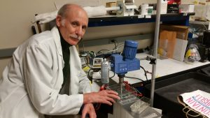 "Richard Rome, MD, working with his machine which creates polymer fiber ""muscles.""   (photo credit: Richard Rome)"
