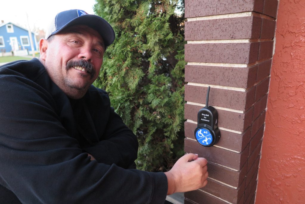 Appleton Wisconsin Alderman Joe Martin utilizes the BigBell to notify the staff inside Mark's East Side restaurant that he needs some assistance with the front door. (photo credit: Inclusion Solutions)